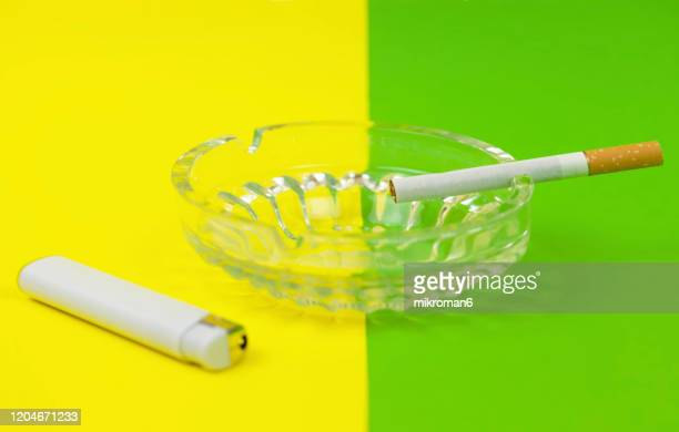 cigarette in ashtray and white lighter - two tone color stock pictures, royalty-free photos & images