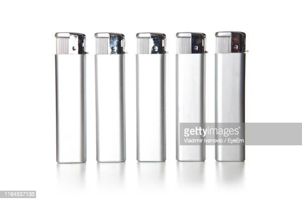 cigarette lighters on white background - cigarette lighter stock pictures, royalty-free photos & images