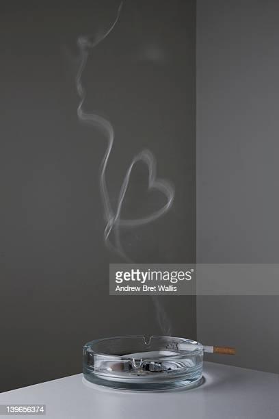 Cigarette on ashtray makes heart-shape smoke ring