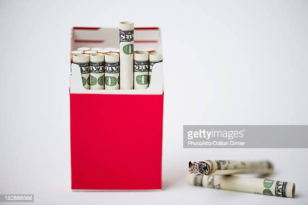Cigarette pack containing rolled dollars