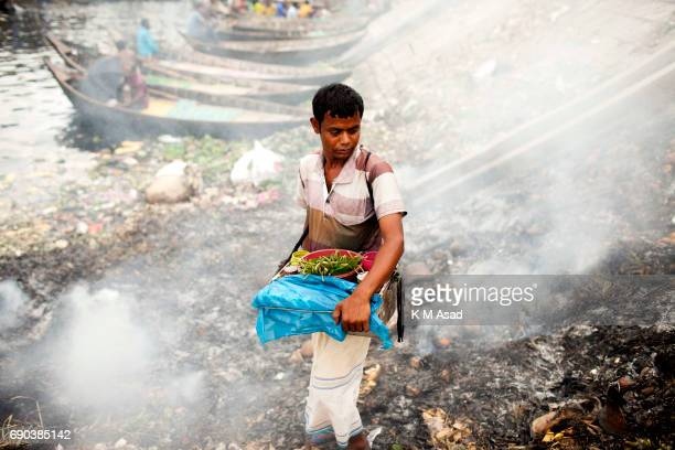 SADARGHAT DHAKA BANGLADESH A cigarette vendor beside the waste burning dumps area producing smoke and toxic pollution at the side of The River...