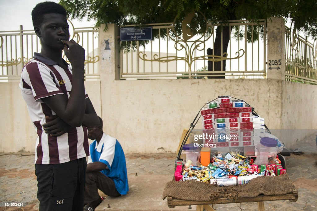 A cigarette vendor waits for customers on a roadside in N'Djamena, Chad, on Wednesday, Aug. 16, 2017. African Development Bank and nations signed agreement to finance a project linking the town of Ngouandere in Cameroon and Chads capital, NDjamena, according to statement handed to reporters in Cameroonian capital, Yaounde in July. Photographer: Xaume Olleros/Bloomberg via Getty Images