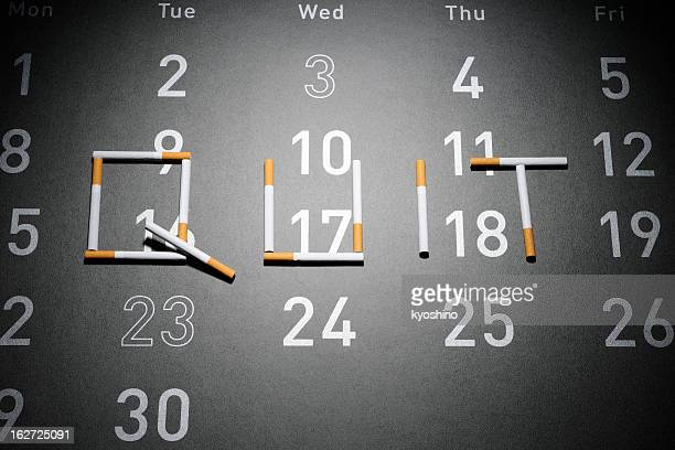 Cigarettes forming the word 'QUIT' on the grey big calendar.