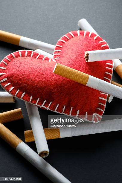 cigarettes lie on a red decorative heart, on a black background. smoking destroys health. social problem. - endopack stock pictures, royalty-free photos & images