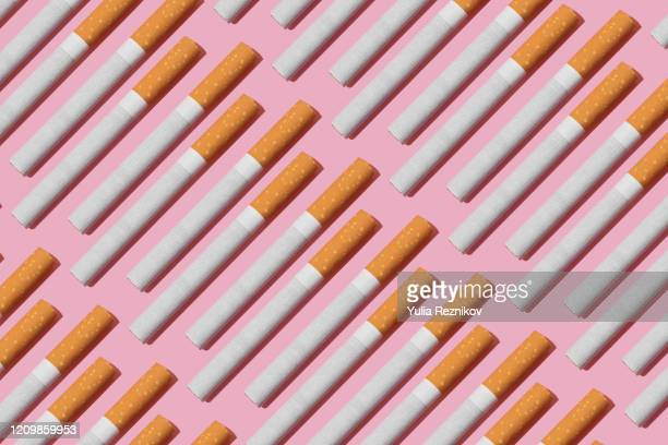 cigarettes on the pink background - cigarette stock pictures, royalty-free photos & images