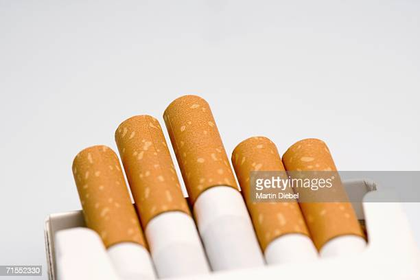cigarettes poking out of open packet - cigarette packet stock pictures, royalty-free photos & images