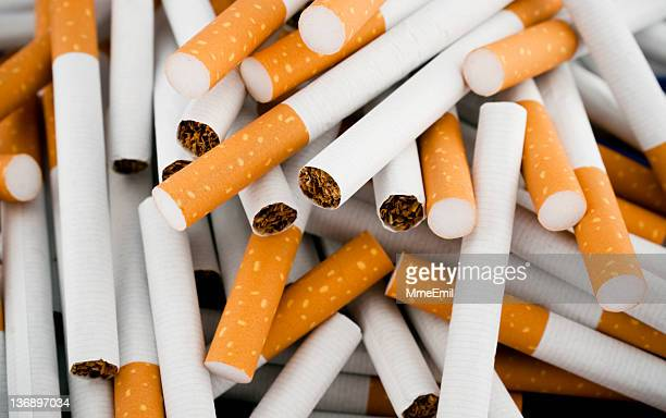 cigarettes randomly piled in a large heap - cigarette stock pictures, royalty-free photos & images