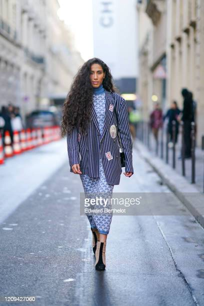 Ciinderella B wears earrings, a hi-neck blue and white fish-scale patterned dress, a navy-blue oversized jacket with white stripes, suede heeled...