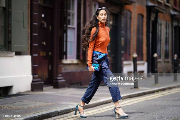 Ciinderella Balthazar wears an orange turtleneck pullover striped cropped pants a blue geometric pattern clutch blue shoes sunglasses during London...