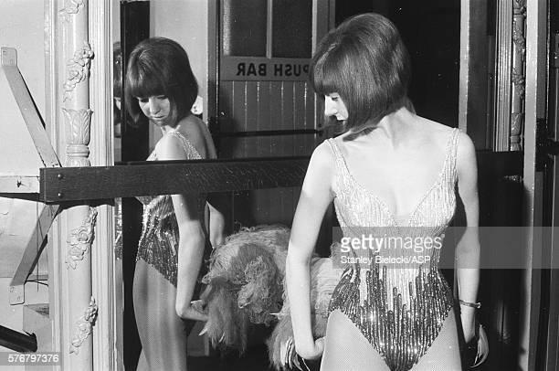 Cilla Black checks her feathered costume in a mirror United Kingdom 1964