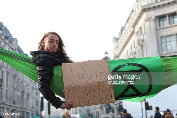 TOPSHOT A cimate change activist in a hammock occupying Oxford Circus in the busy shopping district of central London on April 18 2019 wakes on the...