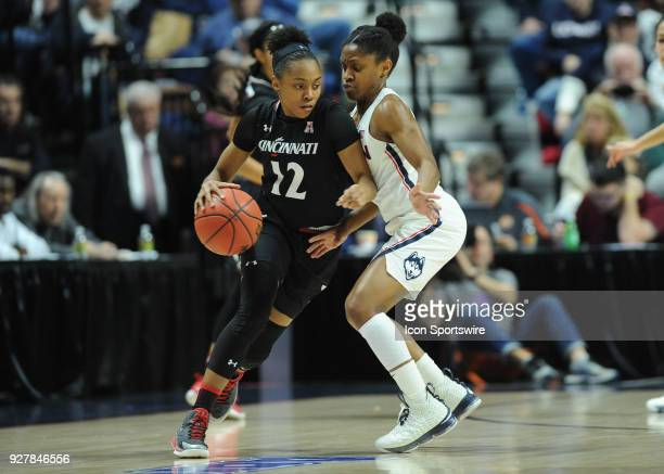 Cincinnati Bearcats Forward Iimar'i Thomas attempts to dribble past the defensive pressure of UConn Huskies Guard Crystal Dangerfield during the game...