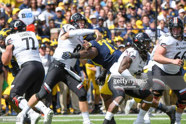 Cincinnati Bearcats quarterback Hayden Moore just gets this pass away as Michigan Wolverines defensive lineman Maurice Hurst hits him during the...