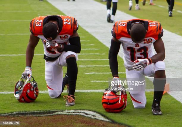 Cincinnati Bengals cornerback Ben Benwikere and wide receiver Kermit Whitfield knell and pray prior to the NFL preseason game between the Cincinnati...