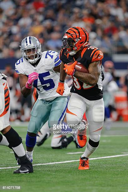 Cincinnati Bengals running back Jeremy Hill looks for a hole in the line of scrimmage as Dallas Cowboys linebacker Ryan Davis chases him during the...