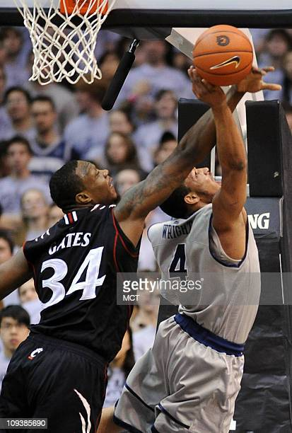 Cincinnati forward Yancy Gates defends a shot attempt by Georgetown guard Chris Wright during firsthalf action at the Verizon Center in Washington DC...