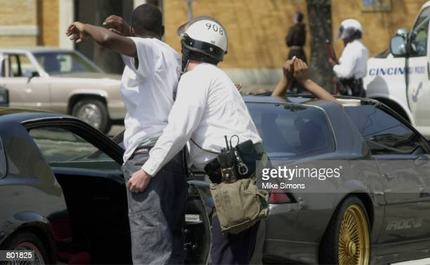 A Cincinnati Police officer pats down the passenger of a car police pulled over after the funeral of Timothy Thomas April 14 2001 in Cincinnati OH A...
