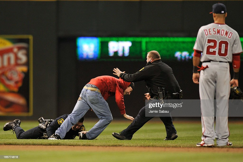 Cincinnati police officers tackle a fan who made it on to the field in the seventh inning of a game between the Washington Nationals and the Cincinnati Reds at Great American Ball Park on April 5, 2013 in Cincinnati, Ohio. Cincinnati defeated Washington 15-0.