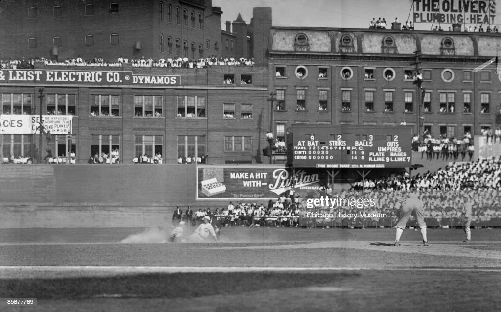 Cincinnati Red Al Neale is out at second base after an attempted sliding steal, during game 2 of the 1919 World Series between the Reds and the American League's Chicago White Sox, held in Cincinnati, Ohio. An unidentified White Sox pitcher is standing on the pitcher's mound in the foreground, leaning forward. Crowds are visible in the outfield bleachers and in windows and on the roofs of buildings farther in the background. From the Chicago Daily News collection.