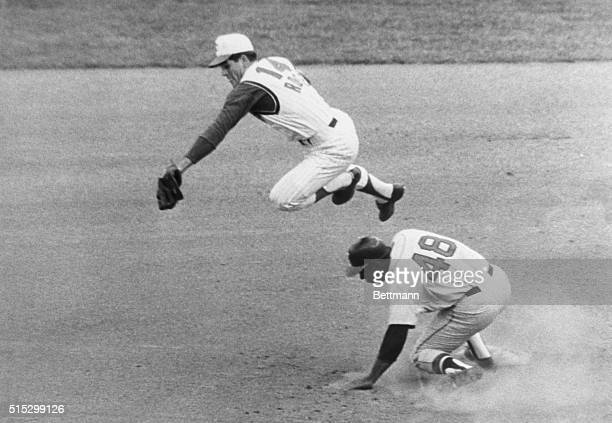 Cincinnati Reds infielder Pete Rose leaps over Mack Jones of the Milwaukee Braves snagging a high pickoff attempt by Reds pitcher Jim O'Toole