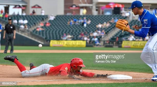 Cincinnati Reds' Juan Perez reaches third before the throw to Kansas City Royals third baseman Garin Cecchini on an RBI triple in the seventh inning...