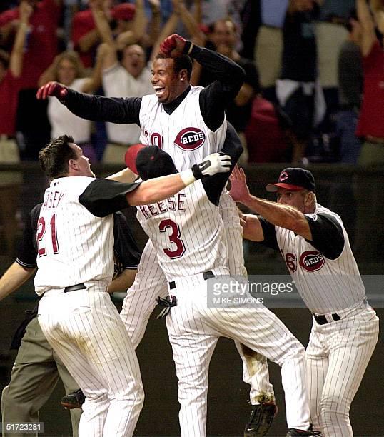 Cincinnati Reds' Ken Griffey Jr celebrates with teammates Sean Casey Pokey Reese and third base coach Ron Oester after scoring the gamewinning...