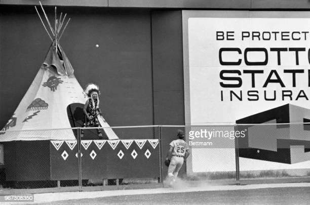 Cincinnati Reds outfielder Bernie Carbo joins Atlanta Braves mascot Chief Hocahoma in watching the ball bounce over the fence for a ground rule...
