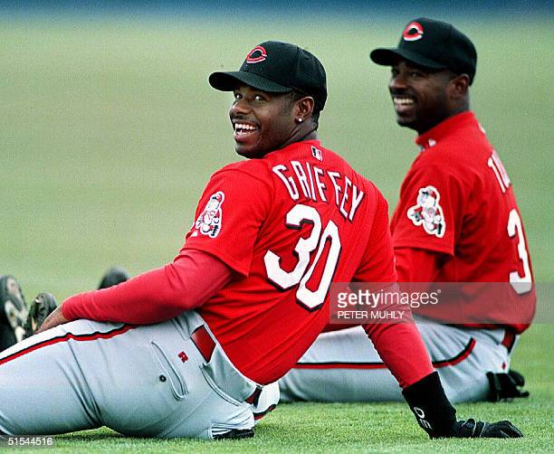 Cincinnati Reds' outfielders Ken Griffey Jr and Michael Tucker share a laugh as they warm up before the start of a spring training game against the...