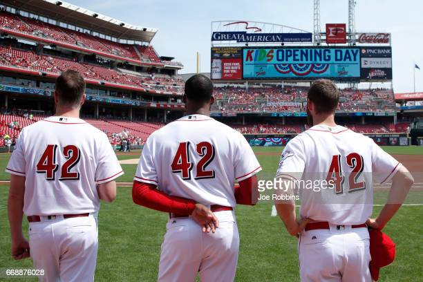 Cincinnati Reds players wear No. 42 in honor of Jackie Robinson Day as they stand for the national anthem prior to a game against the Milwaukee...