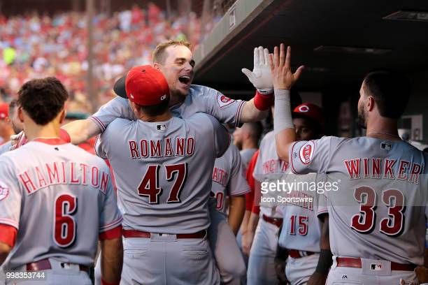 Cincinnati Reds second baseman Scooter Gennett is lifted by teammate starting pitcher Sal Romano as he is congratulated after hitting a solo home run...