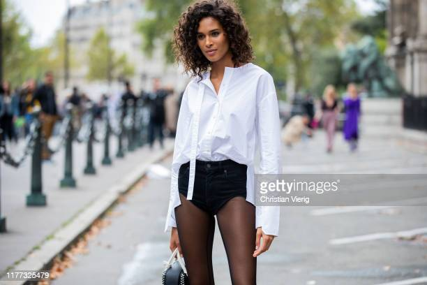 Cindy Bruna is seen wearing sheer tights, black shorts, white button shirt outside Redemption during Paris Fashion Week Womenswear Spring Summer 2020...