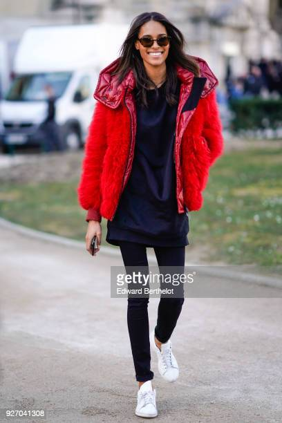 Cindy Bruna model wears sunglasses a redd fluffy bomber jacket black pants during Paris Fashion Week Womenswear Fall/Winter 2018/2019 on March 3 2018...