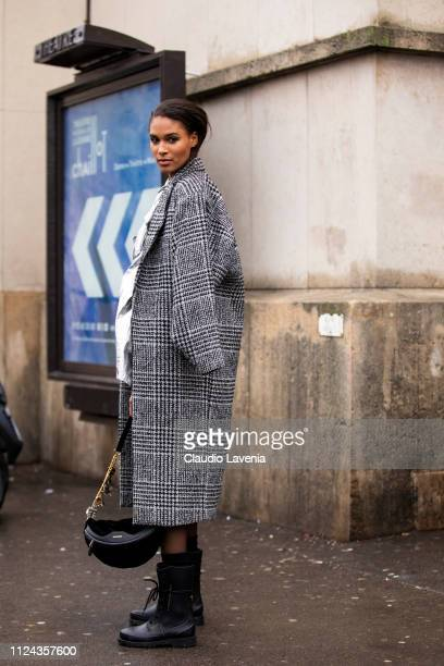 Cindy Bruna, wearing a silver mini dress, black bag, black boots and grey checked coat, is seen outside Elie Saab show during Paris Fashion Week -...