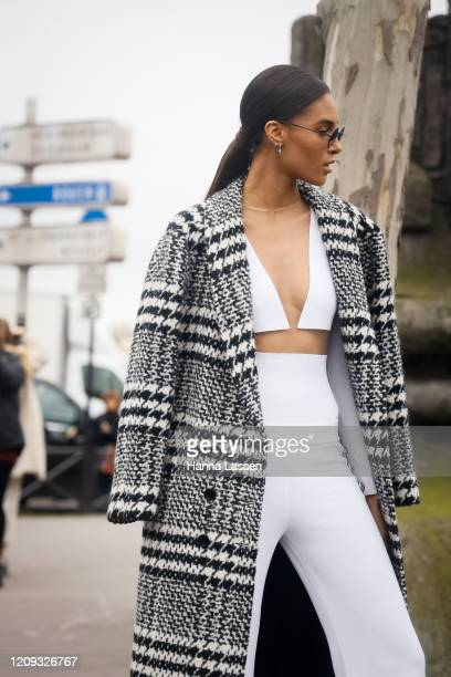 Cindy Bruna wearing plaid black and white coat white twopiece and round sunglasses outside the Balmain show during the Paris Fashion Week Womenswear...