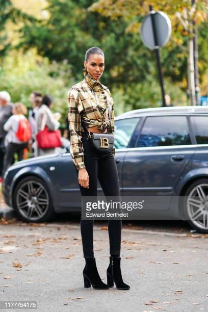 Cindy Bruna wears a checked shirt with ruffles, a Balmain bag, black pants, black shoes, outside Elie Saab, during Paris Fashion Week - Womenswear...