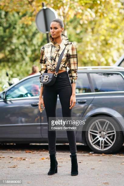 Cindy Bruna wears a checked shirt with ruffles a Balmain bag black pants outside Elie Saab during Paris Fashion Week Womenswear Spring Summer 2020 on...
