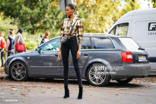 Cindy Bruna wears a checked shirt with ruffles, a Balmain bag, black pants, outside Elie Saab, during Paris Fashion Week - Womenswear Spring Summer...