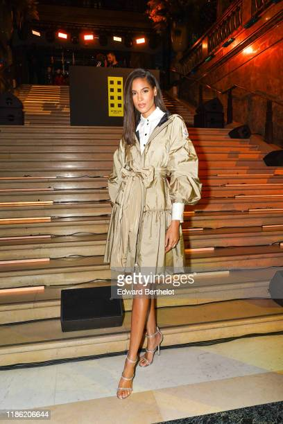 Cindy Bruna wears a pleated trench coat/dress a white shirt during Moncler House Of Genius Paris Opening Event at Galeries Lafayette ChampsElysees on...