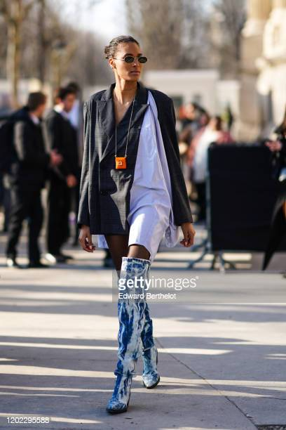 Cindy Bruna wears a white long scarf, a gray blazer jacket/dress, blue and white denim long boots, a Fendi orange mini bag, outside Elie Saab, during...