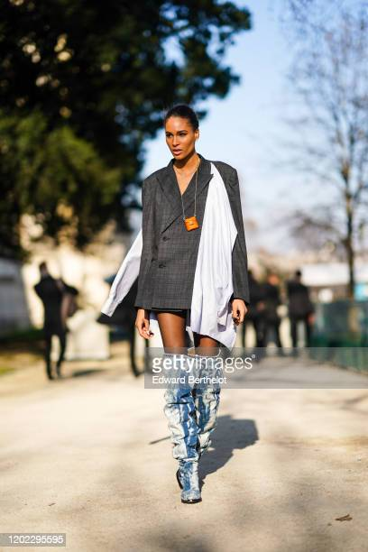 Cindy Bruna wears a white long scarf, a gray blazer jacket/dress, blue and white denim long boots, a Fendi orange mini bag, outside Elie Saab, during...