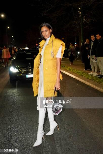 Cindy Bruna wears a yellow long sleeveless puffer jacket, a white dress, white long boots, a bag, outside Moncler during Milan Fashion Week...
