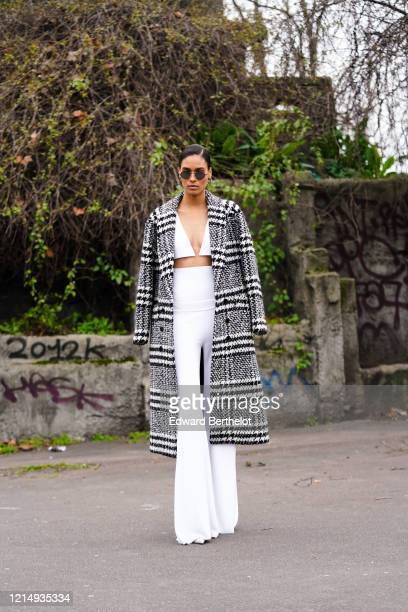 Cindy Bruna wears sunglasses, a gray wool long coat with printed houndstooth patterns, white bras, white flare high pants, outside Balmain, during...