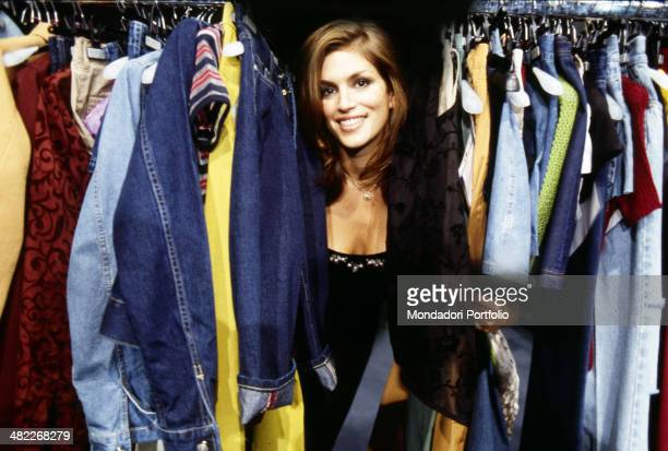 Cindy Crawford smiling in the middle of a rich wardrobe full of clothes the American actress and top model whose trademark is a mole above her lip...