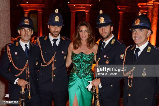 Cindy Crawford wearing poses with police officers at The Green Carpet Fashion Awards Italia 2018 after party at Gallerie d'Italia on September 23...