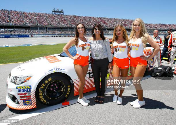 Cindy Elliott poses next to her son's race car with the Hooters Girls prior to the Monster Energy NASCAR Cup Series race on May 7 2017 at Talladega...