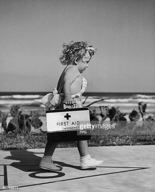 Cindy Lou Sinclair, 19 months, rushing along the seafront in Tampa Bay, Florida, with a first aid kit, circa 1942.