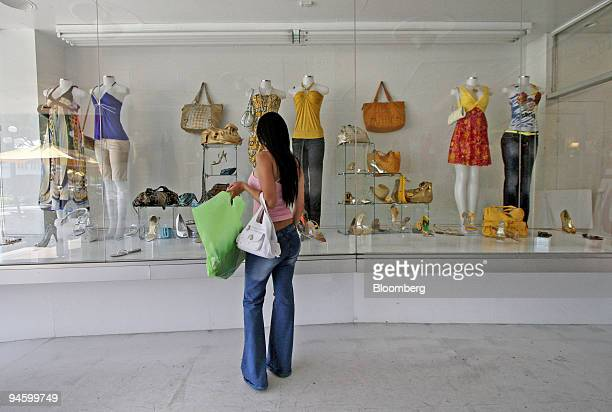 Cindy Mantilla window shops after making a purchase from Vendome in Hollywood Florida Friday June 2007 Consumer spending in the US rose less than...