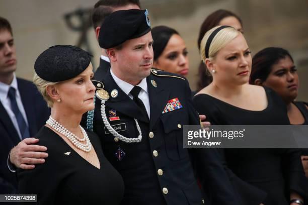Cindy McCain her son James McCain daughter Meghan McCain and Bridget McCain look on as the casket of the late Senator John McCain is loaded into a...