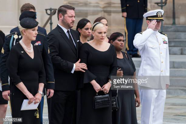 Cindy McCain left the wife of the late Sen John McCain RAriz their son Jack far right daughters Meghan and Bridget second from right watch an Honor...