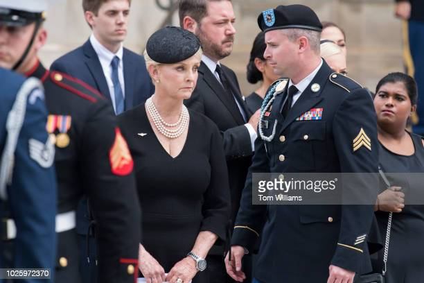 Cindy McCain the wife of the late Sen John McCain RAriz their son Jimmy and daughter Bridget right watch an Honor Guard carry his casket out of the...
